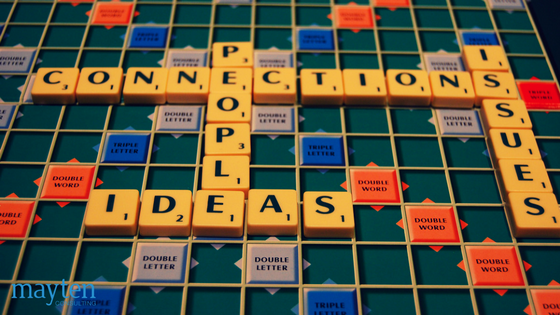 Scrabble game board with interconnecting words: connections, issues, people, ideas